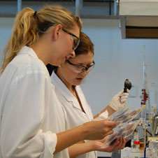 photo of two lab workers in white lab coats