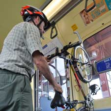 Photo of man loading bike onto light rail