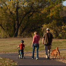 photo of a man, woman, child, and dog walking down a path