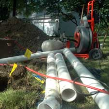 photo of long pipes laid out in a pile on lawn
