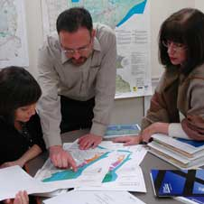 photo of three people consulting maps