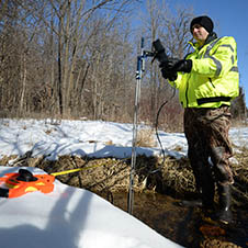 Council employee monitors water quality in local stream.