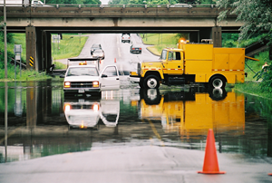 Two trucks in standing water in a paved road under an overpass.