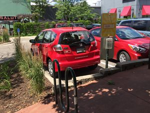 This car sharing vehicle is located in a commercial parking lot, along a transit route, and next to a bicycle rack.
