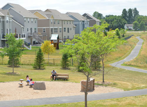 A family plays at Cedarhurst Meadows Park in Cottage Grove's new East Ridgewoods development.