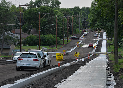 A two-lane road under construction with new curb and sidewalk.