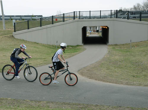 Local kids cruise past the bicycle trail tunnel under Highway 3 near the heart of the Rosemount business district. The tunnel has made bicycle travel much safer in the area near Rosemount High School.