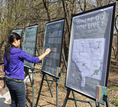 A person places stickers on a board asking for feedback on park activities.