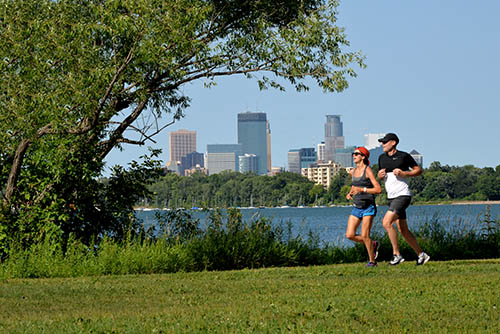 People jogging next to a lake, with the Minneapolis skyline in the background.