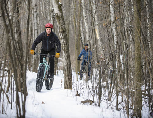 Mountain bikers on snowy trail in the woods