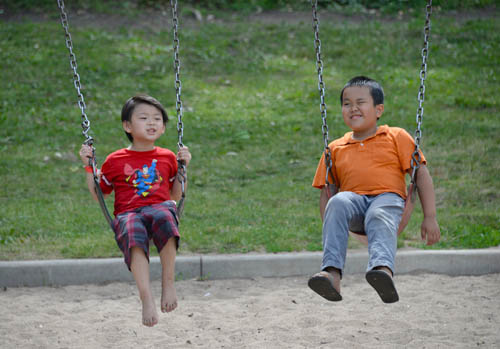 Boys enjoy swinging in a play area at Phalen-Keller Regional Park during Dragon Festival 2016 on July 10.