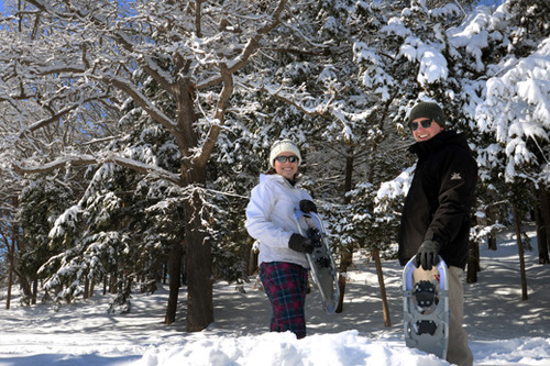 Two people smiling while holding snowshoes next to snow-covered pine trees.