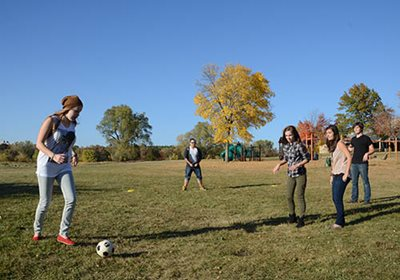 Five teens playing soccer.