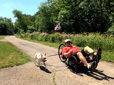 A dog on a leash with a man in a reclining bicycle in a park.