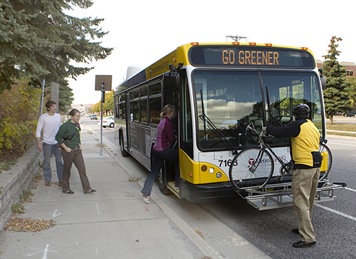 People boarding a bus while another rider removes their bike from the bike rack.