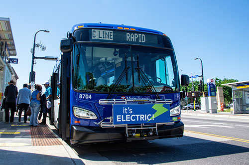 People boarding an electric bus.