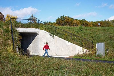 A person walking out of a tunnel under a road.
