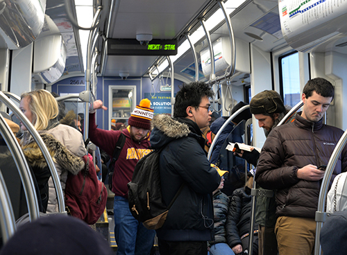 Several people standing inside a crowded light rail train.
