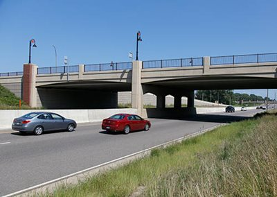 Two cars driving toward a bridge over the divided highway.
