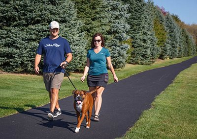 Two people and their dog walking on a paved trail.