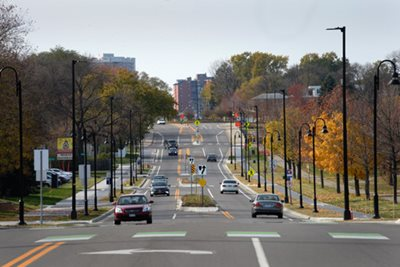 A street with walking paths, bike path, two single lanes of traffic, and a boulevard with turn lanes.