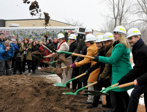 Eight people wearing hard hats, with green shovels. One person is tossing sand into the air.