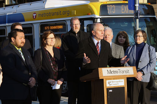 A man speaking at a podium with people and a bus in the background.