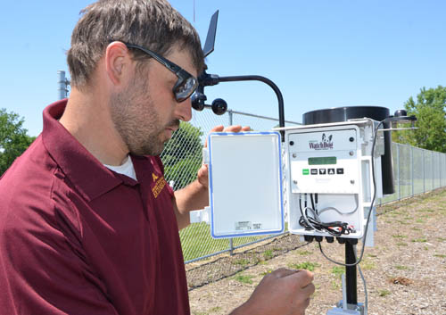Sam Bauer checks a controller for the U's study of the drought resistance of a variety of turf grasses.