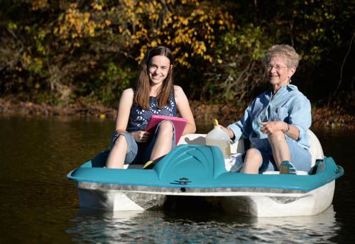 Haley Jostes and Bonnie Juran collect water samples from a small paddleboat.