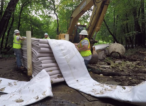 Three workers unfold the liner material for rehabilitating a large sewer pipe.