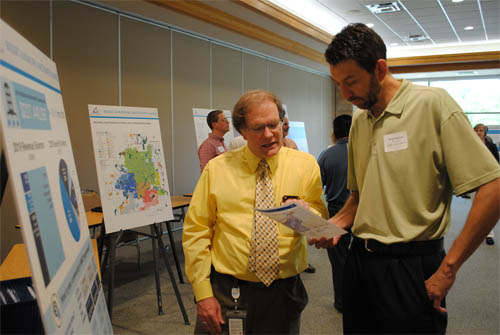 Kyle Colvin, MCES Manager of Engineering Programs, discusses the municipal wastewater charge with Ryan Peterson, Public Works Director for Burnsville at an MCES customer open house.