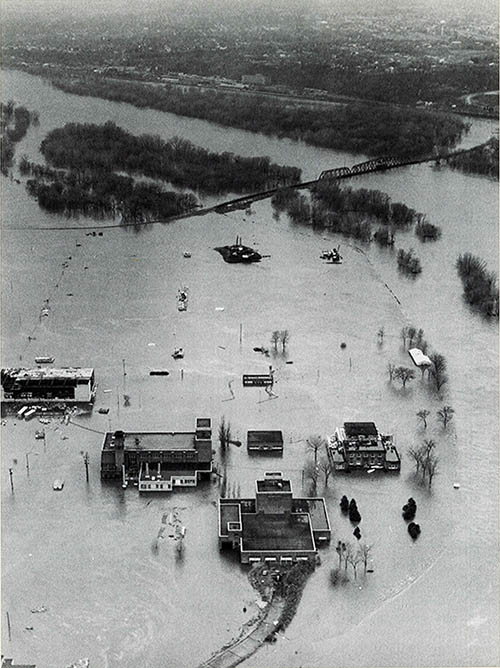 Black-and-white aerial image of a large area of land underwater next to a river.