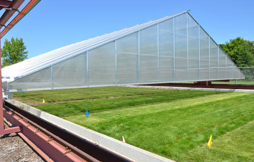 The greenhouse structure travels on rails to cover the test plots when a sensor on its roof detects rain.