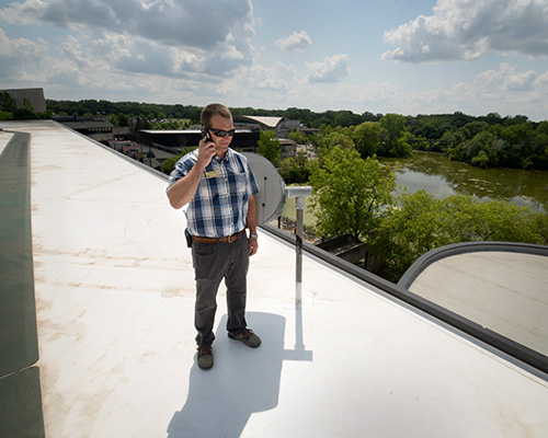 Derik Otten, director of project services at the Minnesota Zoo, on the roof of the Tropical Building, with main pond in the background.