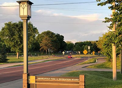 A two-lane road next to a Minneapolis Park & Recreation Board sign.