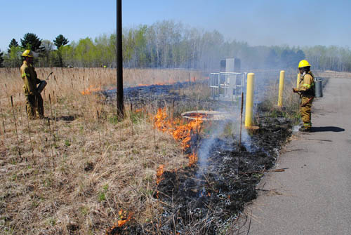 Crews from the contractor Applied Ecological Services work carefully along fence lines, utility equipment and driveways to contain the prescribed burn within specified areas of a reclaimed water discharge site in the City of East Bethel.