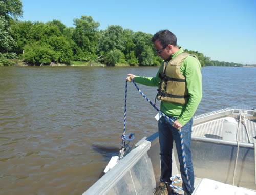A man standing in a boat holding a rope with testing equipment.