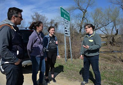 4 people talking at the edge of a road, next to a Vermillion River sign.
