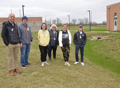 6 people posing in grass near buildings at Empire Wastewater Treatment Plant.