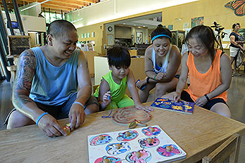 Four people working on a puzzle in a park visitor center.
