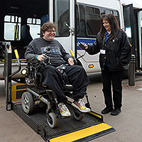 Person in a wheelchair leaving a Metro Mobility van with help from driver.