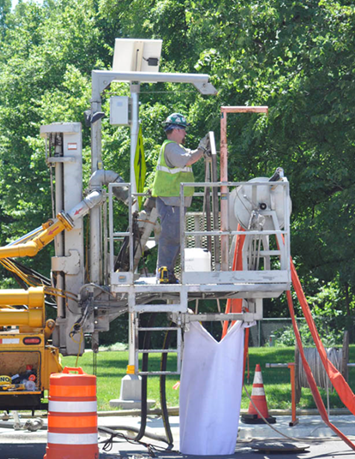 Photo of worker inserting cured-in-place pipe liner into pipe from above a maintenance hole