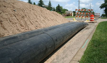 Photo of black temporary conveyance pipes next to a dirt mound and construction barriers.  Pipes run aboveground but may be buried under driveways and roadways to minimized disruption.