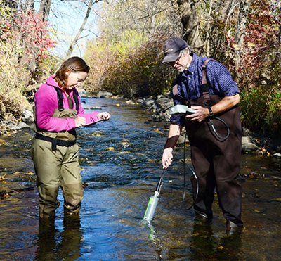Taking water samples from a stream.