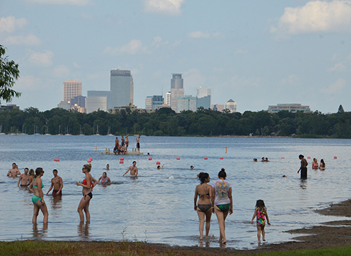 Swimmers at a lake, with the Minneapolis skyline in the background.