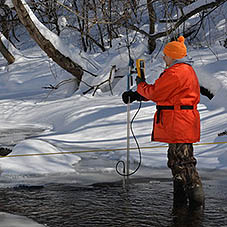 Worker measures water quality in stream.