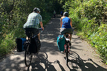 Two people biking on a paved path.