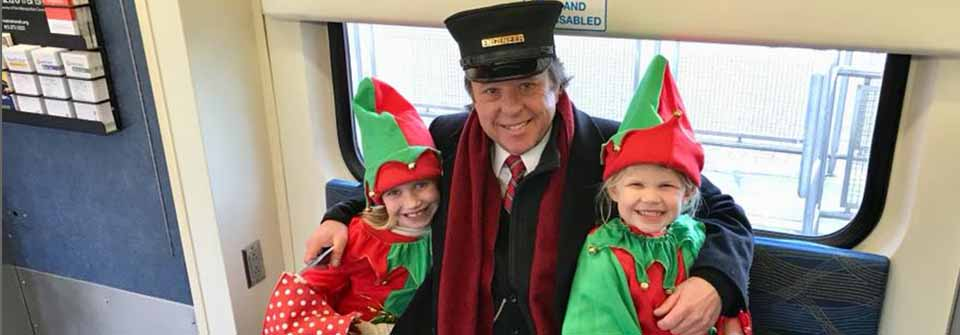 Children dressed as elves with conductor on train.